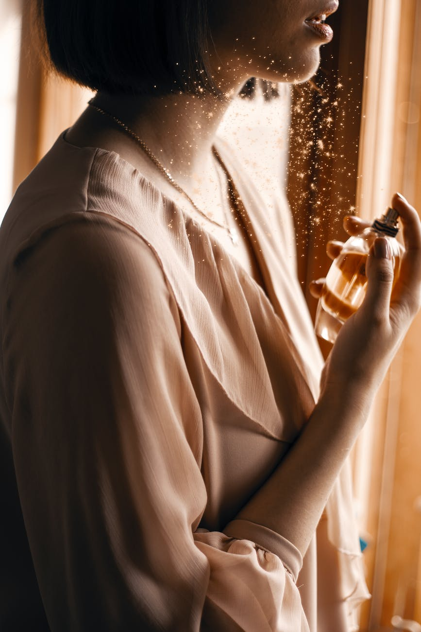 Woman applying perfume.