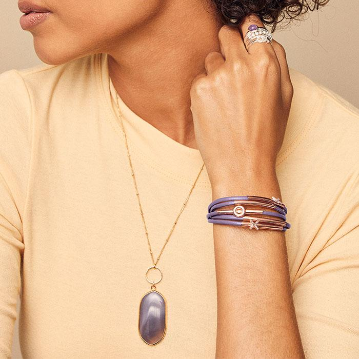 Model wearing the Healing Stone Pendant Necklace, as well as the Charming Stacking Ring Set and Charming Layered Bracelet... all jewelry is available at Avon.