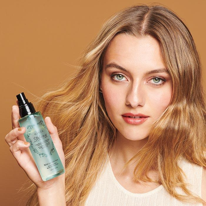 model holding Ginza Stefany Wish You Were Here Hair & Body Mist